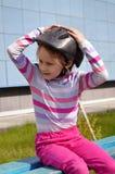 白肤金发的女孩在桃红色牛仔裤在长凳坐在路辗盔甲的一个明亮的夏日在与被举的胳膊的一名镶边制帽工人 免版税库存照片