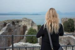 白肤金发的女孩在Grotte的di Catullo西尔苗内 图库摄影