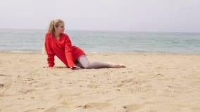 白肤金发的女孩坐沙子由海并且为照片写真摆在 股票视频