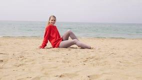 白肤金发的女孩坐沙子由海并且为照片写真摆在 股票录像