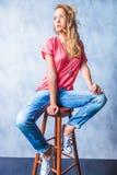 年轻白肤金发的女孩坐看的椅子  免版税库存图片