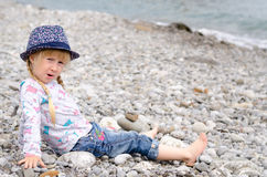 白肤金发的女孩坐看起来的多岩石的海滩担心 免版税库存照片