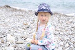 白肤金发的女孩坐看起来的多岩石的海滩担心 免版税图库摄影