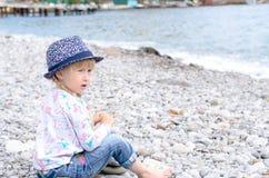 白肤金发的女孩坐看起来的多岩石的海滩担心 库存图片