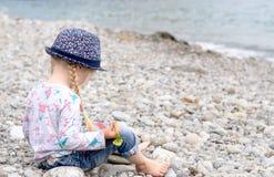 白肤金发的女孩坐看水的多岩石的海滩 库存图片