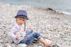 白肤金发的女孩坐看水的多岩石的海滩 免版税库存图片