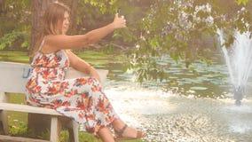 白肤金发的女孩坐长凳由喷泉做Selfie在公园 影视素材
