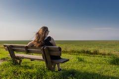 白肤金发的女孩坐长凳 库存照片