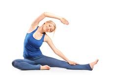 白肤金发的女孩实践的瑜伽 免版税库存图片