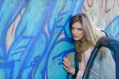 白肤金发的女孩对街道画墙壁 免版税库存照片