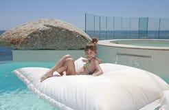 白肤金发的女孩少许池游泳年轻人 库存图片