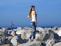 白肤金发的女孩岩石 免版税库存图片