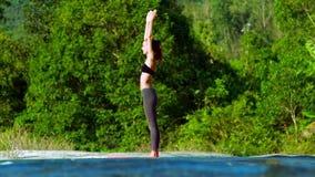白肤金发的女孩弯曲在瑜伽姿势的身体在运行流bankn 股票录像