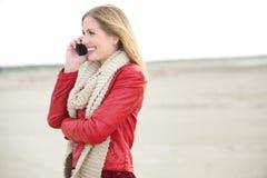 白肤金发的女孩微笑和联系在移动电话 免版税图库摄影