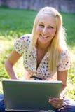 白肤金发的女孩户外膝上型计算机laughiong& 免版税库存图片