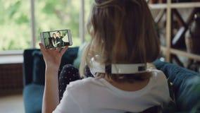 白肤金发的女孩打与智能手机的录影电话谈话与看屏幕和享受现代通信的朋友 股票录像