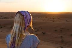 白肤金发的女孩放松在Wahiba沙子的日落,阿曼 免版税库存图片