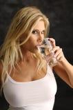 白肤金发的女孩玻璃水 免版税图库摄影