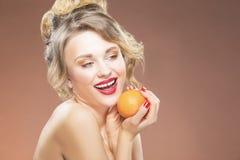 白肤金发的女孩用一橙色果子在手上 摆在反对颜色背景 库存照片