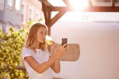 白肤金发的女孩用cellpone饮用的啤酒 免版税库存图片
