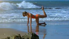 白肤金发的女孩由泡沫似的波浪做在海洋海岸的体育锻炼 影视素材