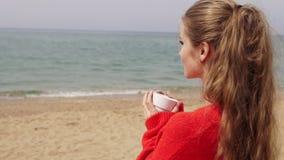白肤金发的女孩由海喝在海滩的茶 股票录像