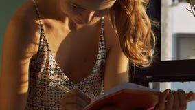 白肤金发的女孩由窗口在日志特写镜头坐写 股票视频