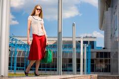 白肤金发的女孩红色性感的裙子微笑&# 免版税图库摄影