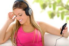 白肤金发的女孩耳机 免版税库存图片