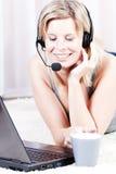白肤金发的女孩联系在耳机。 图库摄影