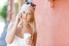 年轻白肤金发的女孩谈话在室外的电话 图库摄影
