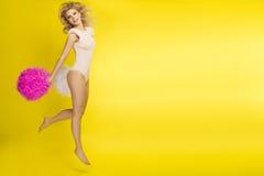 白肤金发的女孩跳,当欢呼与pom pom,黄色背景 库存照片