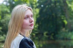白肤金发的女孩头有水和树的 免版税库存图片