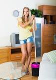 白肤金发的女孩洗涤的镶花地板 免版税库存图片