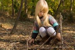 白肤金发的女孩建筑结构用棍子 库存照片