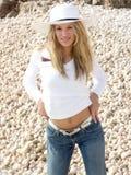 白肤金发的女孩紧紧她的牛仔裤 免版税库存照片