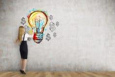 白肤金发的女实业家和电灯泡与美元 免版税图库摄影