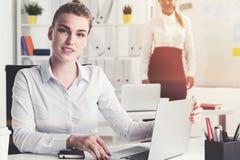 白肤金发的女实业家在有工友的办公室 免版税图库摄影