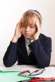 白肤金发的女小学生画象有头疼的 免版税库存照片