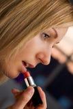 白肤金发的女性她的唇膏使用 免版税库存照片
