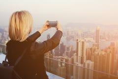 白肤金发的女性旅客做与中国风景手机照相机的照片  库存图片
