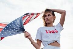 白肤金发的女性模型阻止美国国旗 免版税图库摄影