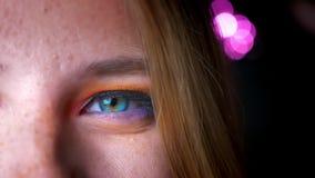 白肤金发的女性特写镜头半画象有天蓝色的眼睛,明亮和五颜六色的构成的在桃红色光背景 影视素材