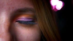 白肤金发的女性特写镜头半画象有蓝眼睛,明亮和五颜六色的构成的在桃红色光背景 影视素材