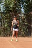 白肤金发的女性网球员垂直的充分的身体画象有球的在室外的法院 免版税库存照片