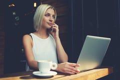 白肤金发的女性自由职业者谈话在手机在便携式的便携式计算机上的工作期间 免版税库存照片