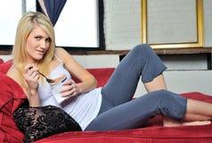 白肤金发的奶油色吃的冰性感的妇女 免版税库存图片