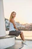 年轻白肤金发的妇女享受日落和坐阿拉尼亚的灯塔的长凳在水附近 免版税库存图片