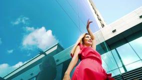 白肤金发的妇女低角度射击红色礼服跳舞的在现代大厦附近 股票视频