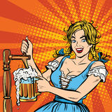 年轻白肤金发的妇女倒啤酒,德国国民服装 库存例证